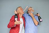 Two Senior Men Celebrating With Champagne