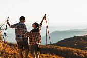 Couple happy together to hike top of mountain and hold trekking sticks.  Amazing autumn view. Travel lifestyle. Success goal achievement.