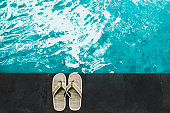 Straw wicker flip flops on edge swimming pool. Made from natural material, sustainable responsibility, disposable. Tropical vacations.