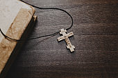 Wooden cross and old bible book on wooden table