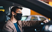 Young attractive fashionable man with protective face mask on driving his car during corona outbreak.
