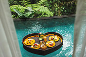 Floating breakfast in jungle swimming pool, tropical resort. Black rattan tray in heart shape, Valentines day or honeymoon surprise, view from above. Exotic summer diet. Tropical beach lifestyle.