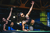 Beautiful woman training at the gym in a group class and doing side planks