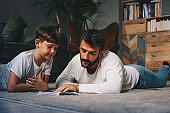 Young attractive father lying down on the floor with his son and studying with him.