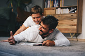 Young father lying down on the floor and reading book to his beloved son.