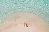 Couple lying on famous pink beach in Komodo national park. Turquoise mint color clear water, tropical vacations on honeymoon. Drone aerial view from above.