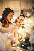 Lovely girls enjoying while decorating Christmas tree.