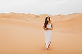 Pretty portrait of young beautiful woman in sand dunes of moroccan Sahara desert. Brunette with long hair, eastern appearance. Bride in white silk dress.