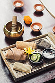 Romantic spa set with lime, scrub, salt, towels and brush in wooden tray. Flower petals in bath tub with foam and candles around. Organic and natural beauty treatment accessories.