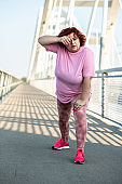 An obese woman does a warm-up exercise on the bridge and wipes the sweat from her forehead with her hand