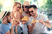 Young friends eating pizza, having fun outdoors.