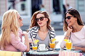Three cute female friends taking a coffee break