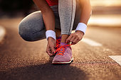 Fitness woman tying sport shoes before running