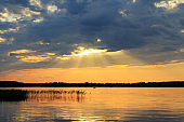 People vacationing in nature or fishermen go by boat on the lake during a beautiful sunset.