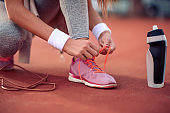 Fitness woman tying shoes before training