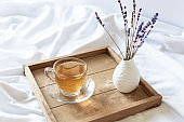 A cup of tea in the morning on wooden tray in bed.