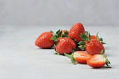 Berries of ripe strawberries on a light surface.