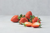 Berries of ripe strawberries on a light surface.  In the foreground, the berry is cut into two halves.