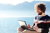 Freelancer workplace at sea beach outdoor. Young man working in traveling. Happy traveler