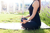 Yoga meditation in park. Young woman doing morning exercise in home garden. Girl breathing fresh air