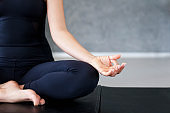 Yoga meditation at home. Young woman practicing exercise. Concept of calmness, relax, healthy lifestyle
