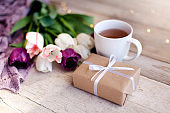 Spring tea. Tulips, gift box and white cup at wooden background. Blooming flowers and present for holiday.