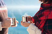 Couple in love drink coffee. Winter picnic at sea beach. Travelers hold camping cups with steamy tea.