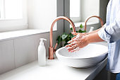 Woman washing hands under water tap. Self care and hygiene. Close up of female hand.