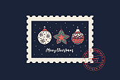 Festive card with Christmas tree toys of various shapes and stamp imprint in style of postage stamps.