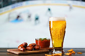 Spicy barbecue chicken wings, tomato salsa, nachos and beer on dark wooden bar table