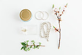 Feminine accessories,marshmallow and jar of cream,parfume and necklace on white background.Spring flowers.Woman fashion jewelry.Flat lay.
