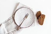 Served table with empty plate,folk and bread on the board.Ready to eat.White background.Top view