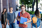 Handsome german male student with group of young adults outdoor in city