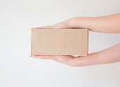 Сourier delivered the package and hands it over to the recipient. Cardboard box with parcel in the hands of a satisfied recipient. Concept of delivery time of goods, fast delivery