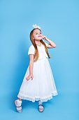 Cute little girl with long hair in white dress holding princess crown on head on blue background.