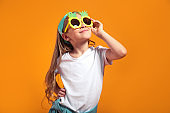 Smiling girl posing in the funny sunglasses and looking away on yellow background