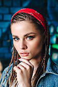 Fashion portrait of young hipster woman with bandana and braids on color wall