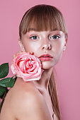 Beauty portrait of beautiful woman model with fresh daily makeup and rose on pink background