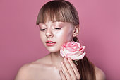 Beautiful woman with natural make-up holding rose.