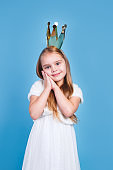 kid girl princess in crown closeup portrait on blue background