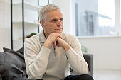 Upset mature man looking at camera at home