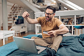 Excited young man shopping online and cheering