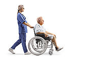 Female nurse pushing an elderly patient in a wheelchair