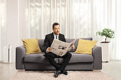 Man in a formal suit sitting on a sofa and reading a newspaper in a living room