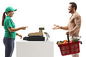 Man paying at a cash register with a shopping basket