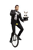 Magician on a unicycle and performing a magic trick with a hat and a rabbit