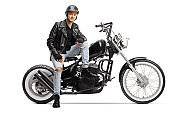 Cool young biker with a helmet and a leather jacket sitting on a chopper motorbike