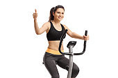 Girl riding a stationary bike and showing thumb up