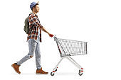 Male student pushing an empty shopping cart