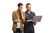 Smiling young man and an auto mechanic looking at a laptop computer